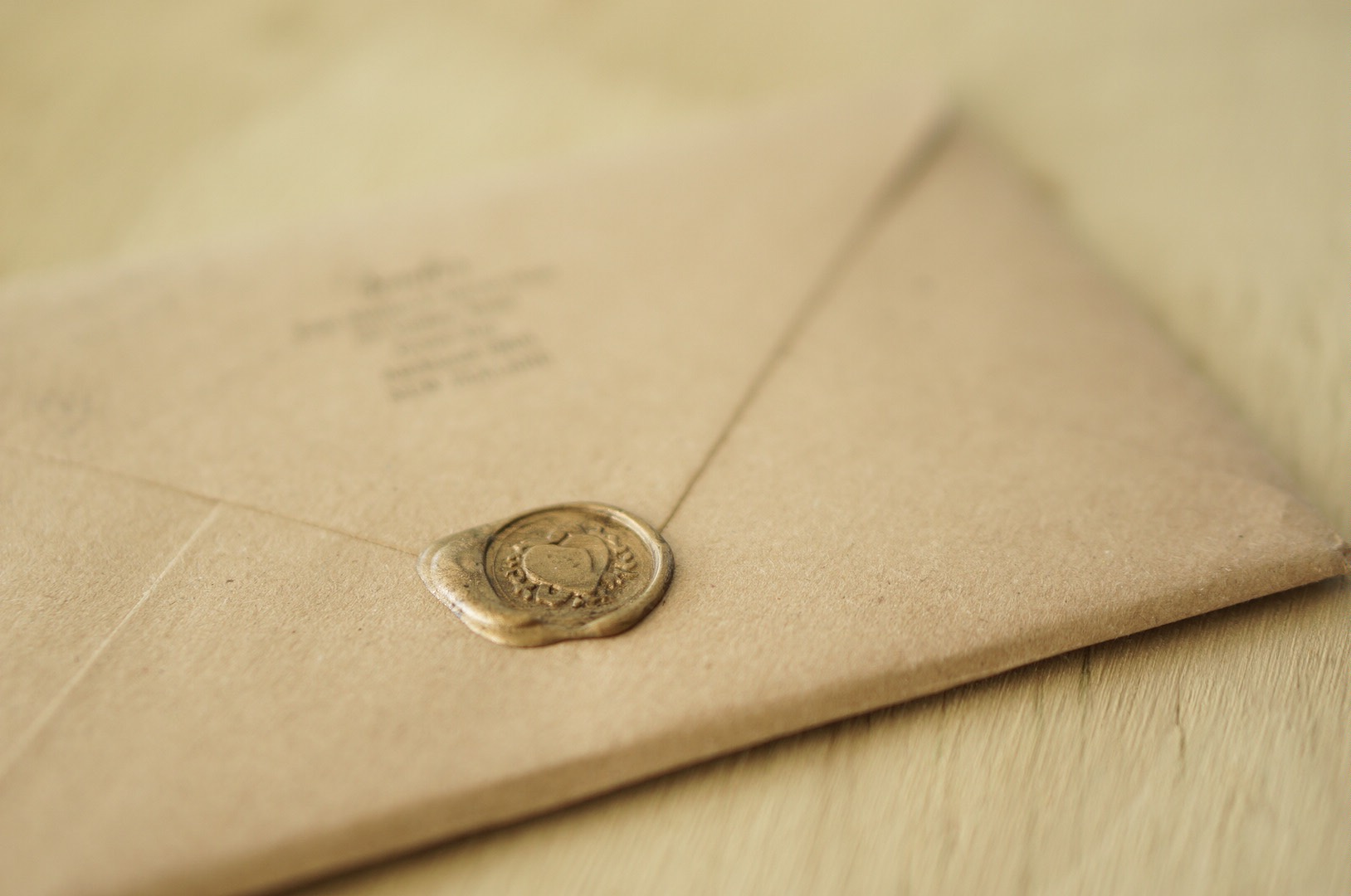 Wedding invitation with gold wax seal on kraft envelope