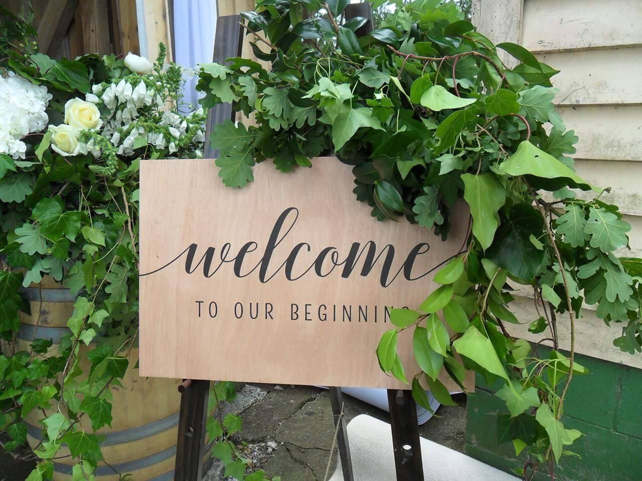 "Wedding ""Welcome to our beginning"" sign on plywood with foliage"