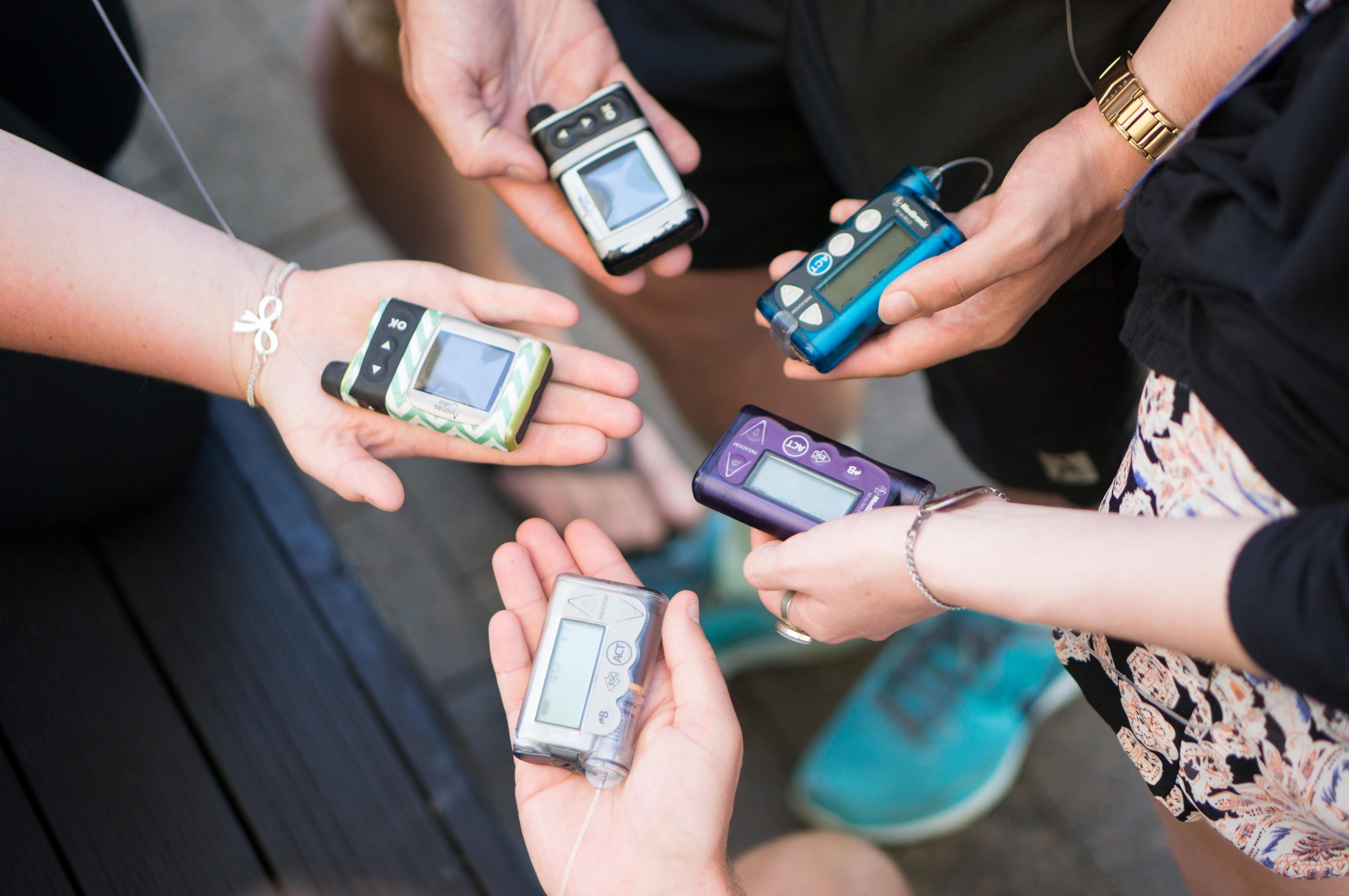 group of teenagers holding insulin pumps